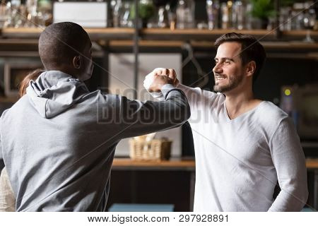 African And Caucasian Buddies Greeting Each Other With Fist Bumping