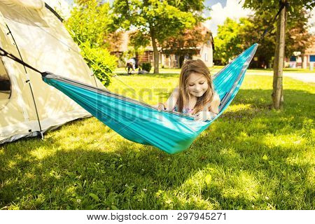 Little Caucasian Girl In The Hammock And The Tent In Background