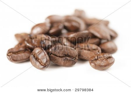 Closeup of coffee bean heap with critical focus on front center bean.