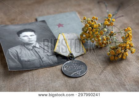 A photograph of a man in military uniform is next to the medal for military merit and a military book. Tansy flowers. Canvas background. poster