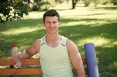 Towards healthier lifestyle. Man smiling face with yoga mat and water bottle sit on bench in park. Join outdoors yoga practice. Athlete with yoga equipment relaxing in park. Man chose yoga outdoors. poster