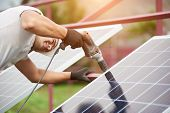 Back view of young technician in helmet connecting solar photo voltaic panel to metal platform using electrical screwdriver on bright sunny summer day.Stand-alone solar panel system installation. poster