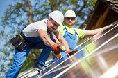 Two professional technicians installing solar photo voltaic panel to metal platform using screwdriver. Stand-alone solar system installation, alternative renewable energy generation concept. poster