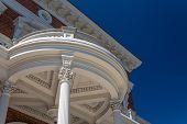 Round exterior portico with Corinthian columns and elaborate details, blue sky, horizontal aspect poster