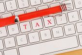 TAX Spelled out on Keyboard with red pen for online tax concept poster