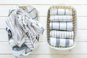 Marie Kondo tidying concept - folded kitchen linens in white basket, top view poster