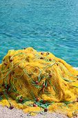 Yellow fishing nets next to the sea poster