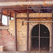 An old disused brick pottery kiln closed off by a fence now, but once used to fire earthenware, stoneware and porcelain poster