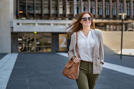 Portrait of successful happy woman on her way to work on street. Confident business woman wearing blazer carrying side bag walking with a smile. Smiling woman wearing sunglasses and walking on street.