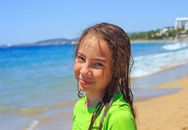 Teen Girl Surfing On Tropical Beach. Child On Surf Board On Ocean Wave. Active Water Sports For Teen