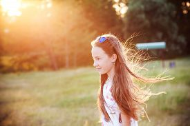 Beautiful Teen Girl Is Enjoying Nature In The Park At Summer Sunset