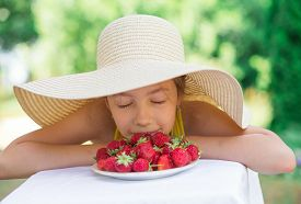 Portrait Of Cute Preteen Girl In Big Hat Is Eating Strawberries At Summer Day