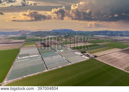 Aerial view of farm fields, storm clouds and the Santa Monica Mountains near Camarillo in Ventura County, California.