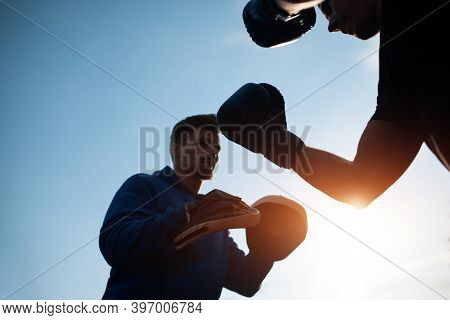 Sport Man Boxing And Exercising In Boxing Gloves With Personal Fitness Trainer