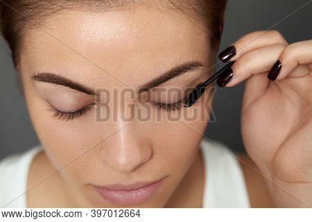 Mascara. Woman Applying Black Mascara On Eyelashes With Makeup Brush. Beautiful Young Woman Face Wit