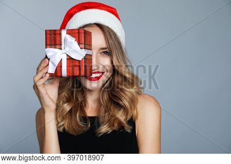 Happy Young Woman Wearing Santa Hat With Christmas Gift On Grey Background
