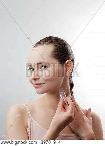 Beautiful Young Woman With Clean Fresh Skin Using The Product For Skin Care. Girl Beauty Face Care.