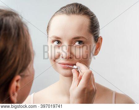 Beautiful Young Woman With Clean Fresh Skin. Beautician Treats Lips. Facial Treatment . Cosmetology