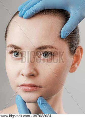 Beauty Treatment For Young Beautiful Female Face, Doctor's Hand In Gloves Touch Face Of Woman Isolat