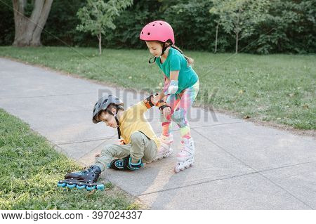 Girl Helping Boy To Stand Up On Roller Blades After Falling. Caucasian Friends Boy And Girl Riding O
