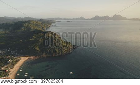 Paradise resort at tropic island aerial. Green forests at mountains of Philippines countryside. Ships and boats at ocean bay shallow water. Sand beach with tropical forested mounts at cottages, houses