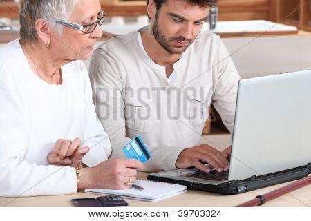 Man helping elderly family member shop on-line