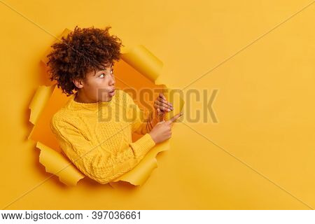 Shocked Young African American Woman Points Away On Copy Space Looks With Impressed Expression Surpr
