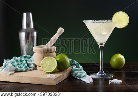 Typical Mexican Margarita Cocktail With Limes And Cocktail Shaker On  Black And Green Background On