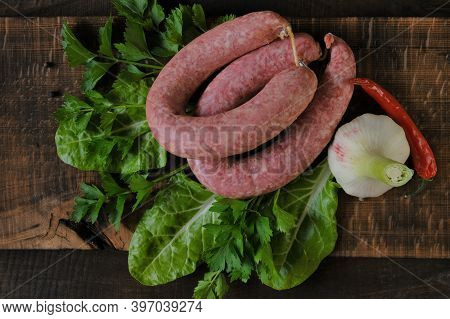 Sausage Ring, Garlic, Chard And Parsley Sprigs,red Chili On Brown Wooden Board On Wooden Table .meat