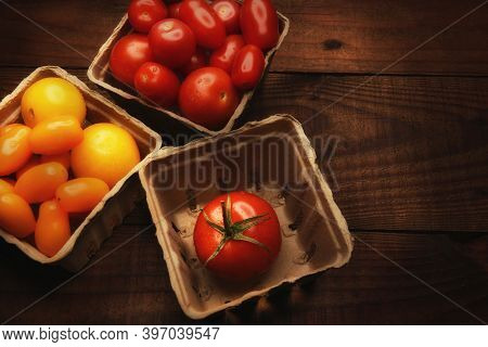 High angle still life of produce baskets filled with a variety of medley tomatoes. Horizontal with warm side light and copy space.