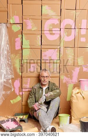 Renewal Refurbishment And Reconstruction Concept. Tired Serious Man Takes Break While Painting Walls
