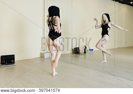 Professional Female Dancer In Black Leotard And Hood Practicing Dance For The Big Show In Front Of M