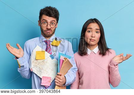 Hesitant Coworkers Shrug Shoulders Collaborate For Making Common Task. Unaware Clueless Students Don