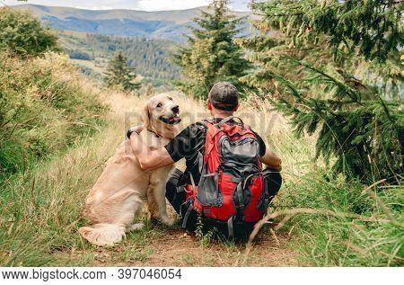 Man on trekking trail next to dog