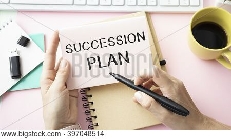 Closeup On Businessman Holding A Card With Text Succession Plan, Business Concept Image With Soft Fo