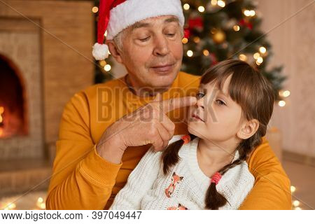 Senior Male In Santa Hat Hugging Hid Granddaughter And Touching Her Nose With Finger, Grandpa Having