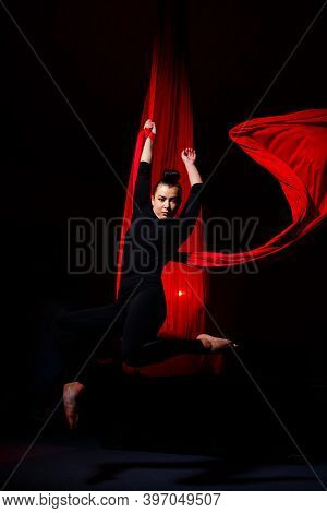 A Sports Girl Performs Gymnastic And Circus Exercises On Red Silk. Studio Shooting On A Dark Backgro