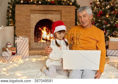 Senior Man In Yellow Shirt Sitting On Floor And Holding Laptop On Knees, Hugging His Granddaughter A