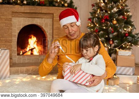 Grandfather And Granddaughter Opening Christmas Presents, Posing In Living Room With New Year Decora