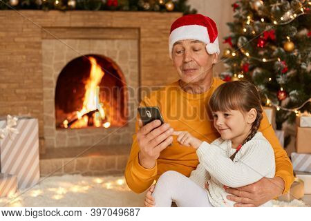 Grandfather And Granddaughter Use Device At Home During Christmas Eve, Old Man With Cute Kid Sit On