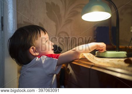 Little Kid Turning Off The Light. Child Turns Off The Lamp