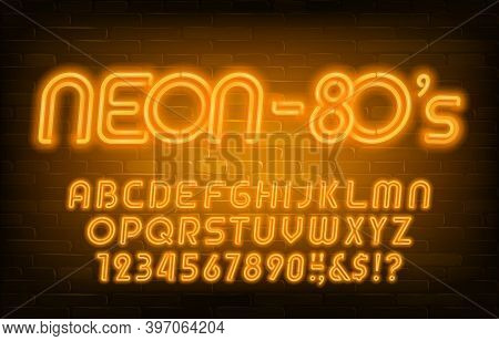 Neon Alphabet Font. Yellow Neon Light Letters And Numbers In 80s Style. Brick Wall Background. Stock