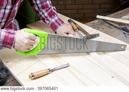 A Carpenter Is Sawing Boards. A Worker Is Sawing A Plank With A Hand Saw. Sawing By The Hand Saw.