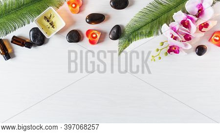 Organic Spa Skincare Products With Essential Oil And Spa Massage Stones Top View On White Wooden Bac