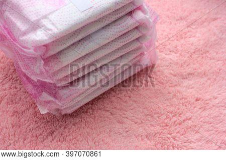 Stack Of Hygiene Feminine Menstruation Pads On Pink Towel Background. Close-up Of Protective Sanitar