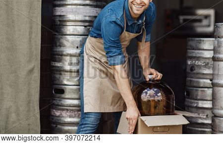 Plant For Production Of Beer. Smiling Handsome Young Worker Man In Apron Takes Out Large Jar For Bre