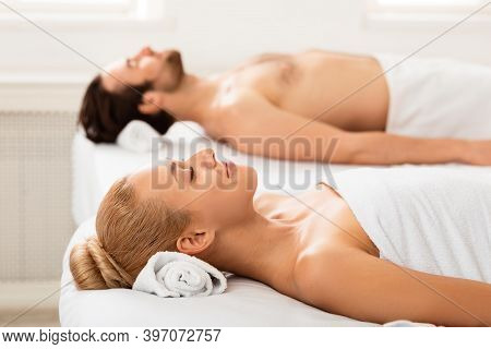 Relaxed Couple After Massage Therapy Lying On Towels Relaxing Indoors After Beauty Treatment. Romant