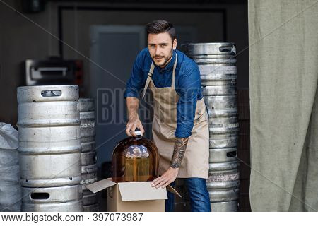 Worker In Brewery Warehouse. Handsome Strong Young Employee In Apron Pulls Out Large Jar With Ingred