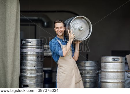 Modern Brewery And Worker With Keg On Plant, Small Business And Beer Industry. Smiling Handsome Youn