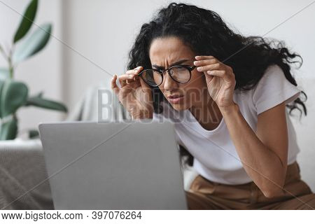 Young Woman Freelancer With Bad Eyesight Using Laptop, Trying To Work From Home, Copy Space. Curly L